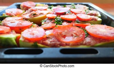 women's hands, spread thin tomato slices on stuffed...