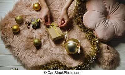 Womens hands straighten a bow on a gift box lying on a fur skin around tinsel and gold colored Christmas decorations. Festive background. Preparing for Happy Winter Holidays. Merry christmas and new year. Close up. Slow motion