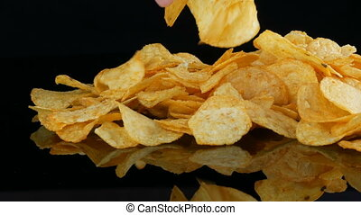 Women's hands take potato chips lie on a mirror surface...