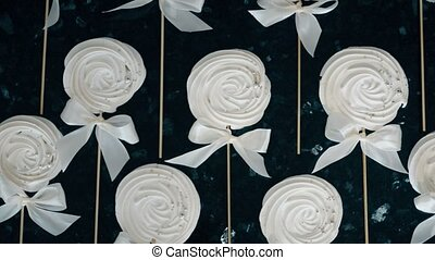 Women's hands tied a bow on a number of meringue on a stick.
