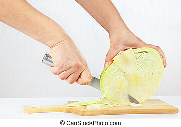 Women's hands with a knife shred cabbage on a cutting board