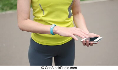 Women's hands with a sports bracelet and smart phone...
