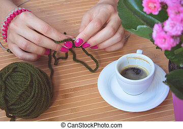Women's hands with purple manicure are knitted metal spokes of a wooden table