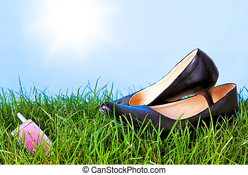 Womens high heel shoes and mobile phone on grass