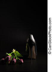Women's high-heeled shoes and a bouquet of tulips on a black background.