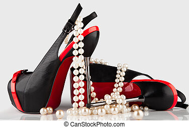 women's high-heeled shoes and a pearl necklace