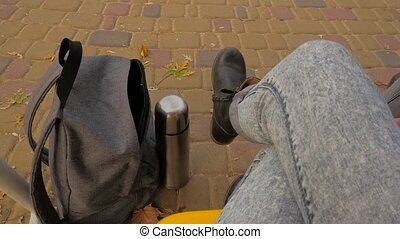 Women's legs are swinging on a swing. Autumn, thermos, legs,...