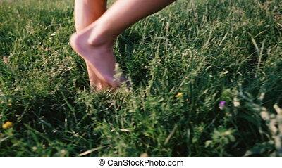 Women's legs go on the green grass