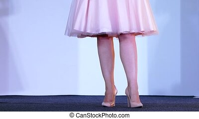 Women's legs in a dress and on heels stand on a podium -...