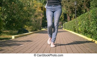 women's legs in jeans and sneakers are on a paved path.
