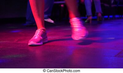 Women's legs in silvery shoes are dancing on the dance floor in the disco bar. Light from safitov. 4k