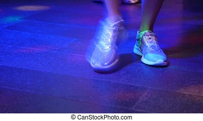 Women's legs in silvery shoes are dancing on the dance floor in the disco bar.
