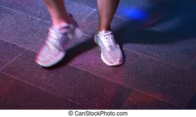Women's legs in silvery shoes are dancing on the dance floor...