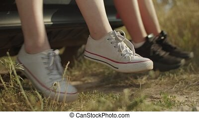 Close-up of women's legs in trendy sneakers dangling from car trunk during summer vacations road trip in countryside. Joyful female travelers enjoying outdoor leisure and freedom during car trip.