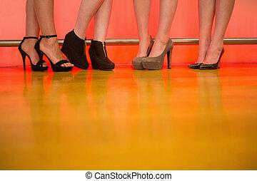 Womens legs wearing high heels at a bar of nightclub