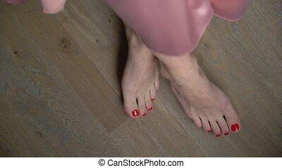 Women's legs with red pedicure. Women's feet sitting...