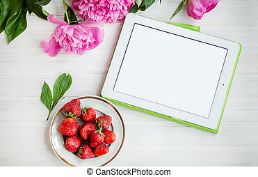 Women's office workplace with strawberries and flowers. Mockup with digital Tablet PC.