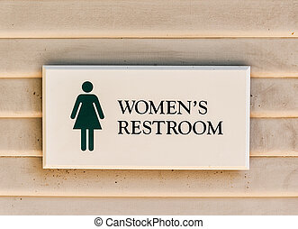 Women's restroom sign on grunge wooden wall