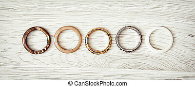 Women's rings arranged in a row on the wooden backround