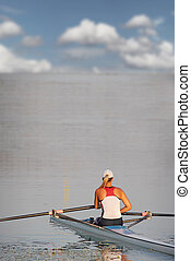 A young woman in a boat ready to start waiting in rowing race