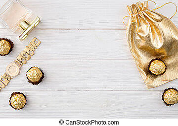 Women's set of accessories and sweets in golden color on wooden background: perfume, candy, chocolate, watch, jewelry, golden bag