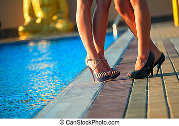 Women's slender legs on the background of the pool