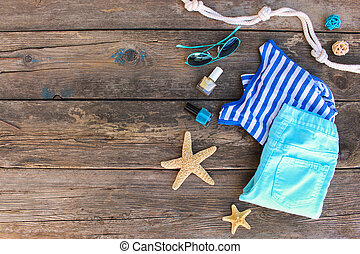 Women's summer clothes and accessories on old wooden background. Top view, flat lay.