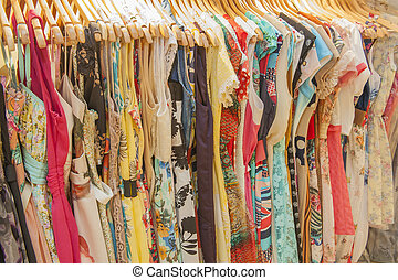 Variety of colorful womens summer fashion clothes hanging on rail in retail shop