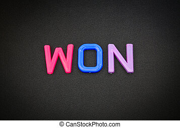 Won in colorful toy letters on black background