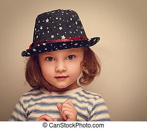 Wonder kid girl in trendy hat looking. Closeup vintage portrait
