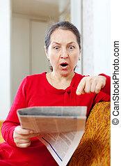 wonder mature woman with newspaper