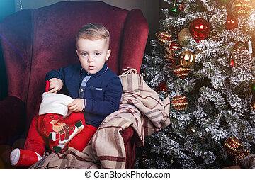 wondered little boy holding a christmas stocking