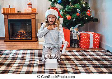 wondered, und, erstaunt, kind, sitzen knien, und, anschauen, geöffnet, weißes, box., sie, hält, oberseite, von, ihm, in, hand., kind, hält, oberseite, von, kasten, in, hand., dahin, ar, kaminofen, und, weihnachtsbaum, mit, geschenke, hinten, sie.