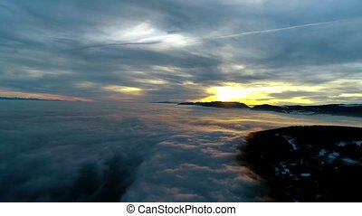 Wonderful aerial drone panorama flyover in orange warm evening sunset sky over dense fog cloud mountain hill landscape