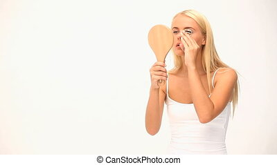Wonderful blond woman plucking her eyelashes