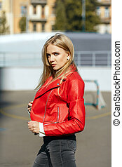 Wonderful blonde girl with long hair wearing red leather jacket posing in sun light