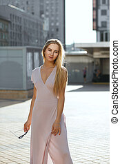 Wonderful blue eyed woman with long hair wearing pink dress posing in sun glare
