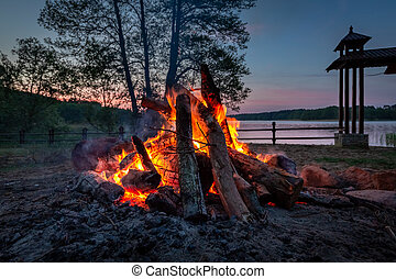 Wonderful bonfire at dusk by the lake in summer