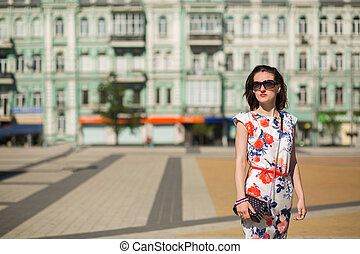 Wonderful brunette girl wearing trendy dress and glasses, posing at the street. Space for text