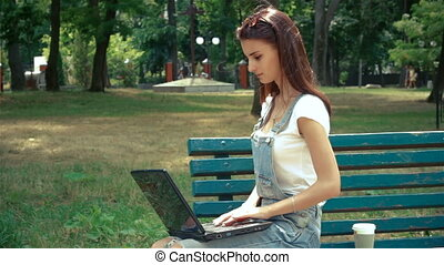 wonderful brunette sitting on a bench with a laptop