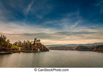 Wonderful castle by the lake in autumn at dusk