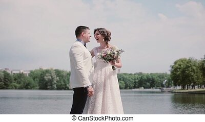 Wonderful couple in love on their wedding day standing on a river bank, laughing happily. Sunny day in summertime.