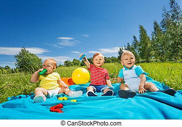 Wonderful cute toddlers sit on blanket in field