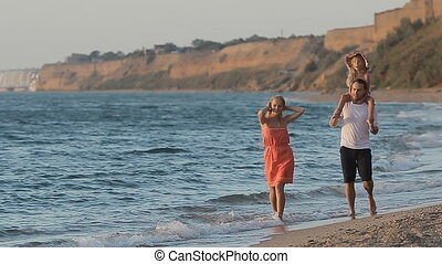Wonderful family with little daughter sitting on the shoulders of father walking along the beach in slow motion