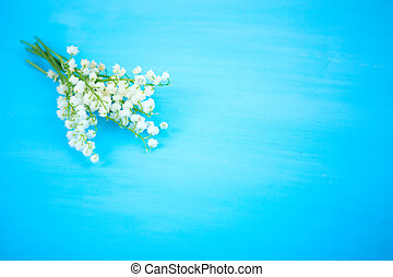 Wonderful fragrant white flowers with a delicate scent. lilies of the valley on a blue wooden background