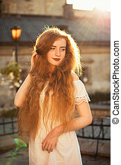 Wonderful ginger young woman with naked long wavy hair posing in sun glare at sunset