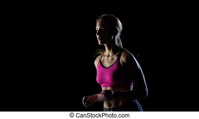 Wonderful lass is running on a black background. Slow motion