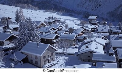 Wonderful little cozy house cottage villa in snow covered village in the Alps mountains on white sunny winter aerial day