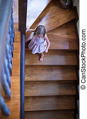 Wonderful little girl on the stairs in a big house