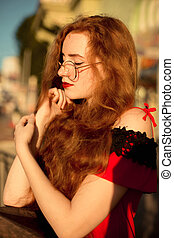 Wonderful red haired girl with long curly hair posing at the avenue in the evening